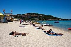 Een grote groep die mensen op een zandig strand ontspannen royalty-vrije stock foto's