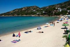 Een grote groep die mensen op een zandig strand ontspannen stock afbeelding
