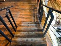 Een grote houten bruine trap die neer met stappen en traliewerk leiden De achtergrond stock fotografie