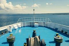 Een grote katrolschijf met gerolde tros op het open dek van de veerboot op de zeegezichtachtergrond De zomercruise in Griekenland stock afbeelding
