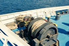 Een grote katrolschijf met gerolde tros op het open dek van de veerboot De zomercruise in Griekenland royalty-vrije stock foto's