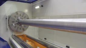 Een grote lange staalschacht wordt machinaal bewerkt op een moderne CNC draaibank stock video
