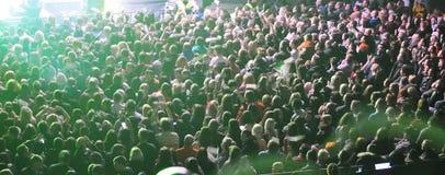 Een grote menigte van mensen bij een overleg in de stralen van kleurenmuziek royalty-vrije stock foto's
