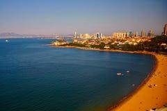 Een grote mening van blauwe overzees, krulkust, gouden strand en stadsgebouwen royalty-vrije stock afbeelding