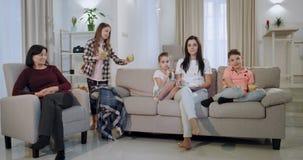 In een grote moeder van de familieoma en drie jonge geitjes die op een TV letten samen het grote meisje brengend het sap aan haar stock videobeelden