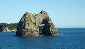 Een grote overspannen rots die de oceaan toenemen Royalty-vrije Stock Foto