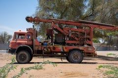 Een grote rode oude antiquiteit opgesplitste die vrachtwagen van de watermachine in het zand door bomen in de Verenigde Arabische royalty-vrije stock afbeelding