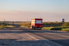 Een grote rode vrachtwagen vervoerden goederen op een weg over lange afstand stock foto
