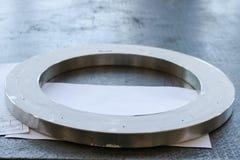 Een grote ronde glanzende metaalring met prikken, gaten, een flens op de werkende ijzerlijst in de fabriek, de workshop royalty-vrije stock foto's