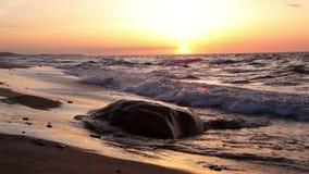 Een grote rots op het strand bij zonsondergang stock video