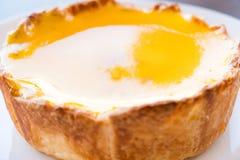 Een grote scherpe kaas vult met oranje jam klaar om op witte pla te eten Stock Afbeeldingen