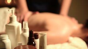 Een grote therapeut van de kerelmassage doet een massage die voor een jong meisje op het bankgezicht neer in een donker bureau me stock video