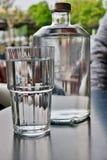 Een grote transparante fles water met een volgende glas, close-up royalty-vrije stock foto's