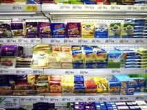 Een grote verscheidenheid van kaasproducten op vertoning bij een kruidenierswinkel slaat klaar aan verbeterd op door klanten Stock Foto