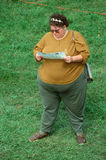 Een grote vrouw die een pamflet leest royalty-vrije stock afbeeldingen