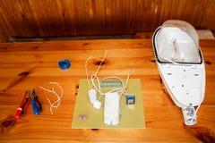 Een grote witte gedemonteerde straatlantaarn met een elektrokring met draden en vervangstukken, installatiemateriaal, buigtang royalty-vrije stock fotografie