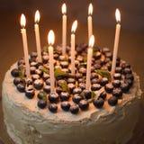 Een grote witte verjaardagscake met verse organische bosbessen en munt en witte kaarsen op de bovenkant Stock Foto's