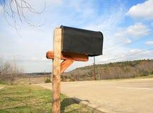 Een grote zwarte U.S brievenbus naast de weg stock foto