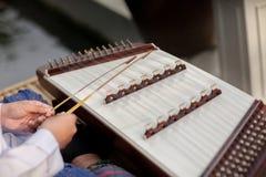 Een hakkebord dat Thais traditioneel muziekinstrument Mens die gehamerd hakkebord met houten hamers spelen royalty-vrije stock afbeelding