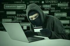 Een hakker die online creditcard stelen stock afbeeldingen