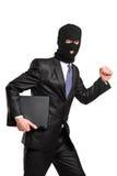 Een hakker in diefstalmasker dat met laptop loopt Stock Foto