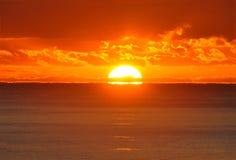 Een halve zon toont over oceaan bij zonsopgang Stock Foto's