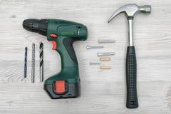 Een hamer, een draadloze boor met een reeks beetjes, verscheidene schroeft bouten, pennen en stoppen op witte houten achtergrond Stock Afbeelding