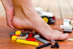 Een hand die één of andere massage op een hiel van voeten na stap op legos, gekleurde blokken maken royalty-vrije stock afbeeldingen