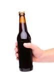 Een hand die een bruine bierfles steunen stock fotografie