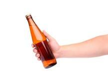 Een hand die een gele bierfles steunen stock foto's