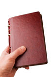 Een hand die een notitieboekje houdt Stock Fotografie