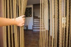 Een hand die een vlieg openen die deurgordijn tegenhouden Royalty-vrije Stock Afbeelding