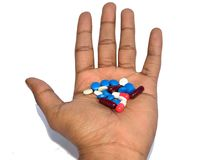 Een hand die kleurrijke pillen houden stock afbeelding