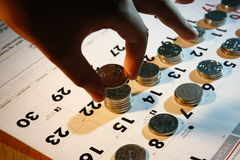 Een hand die Muntstukken/Geld op een Kalender stapelt Stock Foto's