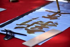 Een hand die een penseel houden schrijft met het gouden couplet van de inktlente De vertaling van karakter is Nieuwjaar stock fotografie