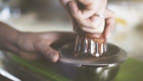 Een hand die sap van een sinaasappel op een handglaspers drukken Stock Foto
