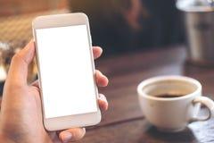 Een hand die witte mobiele telefoon met het lege Desktopscherm en koffie houden vormt op houten lijst in moderne koffie tot een k Royalty-vrije Stock Afbeelding