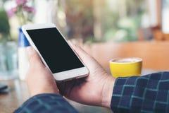 Een hand die witte mobiele telefoon met het lege zwarte Desktopscherm en gele koffie houden vormt op houten lijst in moderne koff Stock Foto