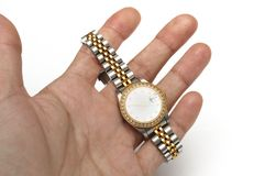 Een hand die een zilveren en gouden dameshorloge met een rond horlogegezicht en diamanten op de rand houden stock foto