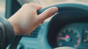 Een hand duwt de knoop van de cruisecontrole op een stuurwiel stock videobeelden