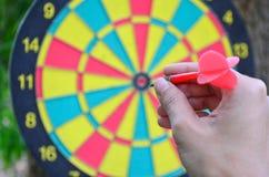 Een hand een pijltje houden die wordend klaar om naar het dartboard te streven Stock Foto