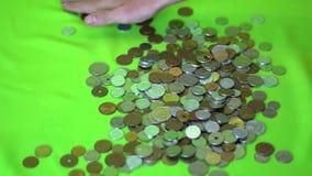 Een hand grijpt heel wat internationale muntstukken en glijdt het naar hem op een groene achtergrond Langzame Motie stock footage