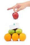 Een hand houdt een appel op fruitpiramide Stock Foto's