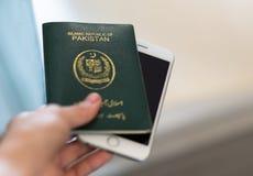 Een hand houdt het paspoort van Pakistan Nadruk op de doopvont op paspoort Stock Foto