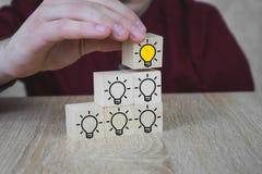 Een hand houdt een kubus met een brandende lamp wanneer alle andere lampen worden gedoofd, die het Nieuwe Idee, de concepten van  stock afbeelding