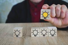 Een hand houdt een kubus met een brandende lamp wanneer alle andere lampen worden gedoofd, die het Nieuwe Idee, de concepten van  stock foto's