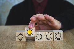 Een hand houdt een kubus met een brandende lamp wanneer alle andere lampen worden gedoofd, die het Nieuwe Idee, de concepten van  stock afbeeldingen
