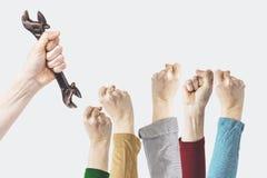 Een hand houdt een moersleutel, de fotografieconcept van de arbeidsdag, close-up van de opgeheven vuist van een jonge vrouw stock foto's