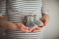 Een hand houdt een paar kleine schoenen Het ` s schoenen voor zuigeling op grijze achtergrond Moeder en babythema Zwangere vrouw royalty-vrije stock fotografie