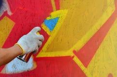 Een hand met een aërosol die een nieuwe graffiti op de muur trekt royalty-vrije stock afbeelding